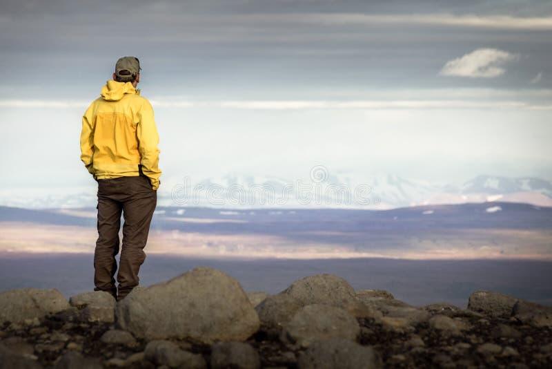Equipaggi la condizione sulla montagna, sembrante rilassata verso catena montuosa nevosa immagini stock libere da diritti
