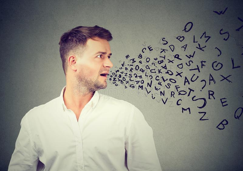Equipaggi la conversazione con le lettere dell'alfabeto che escono dalla sua bocca immagini stock libere da diritti