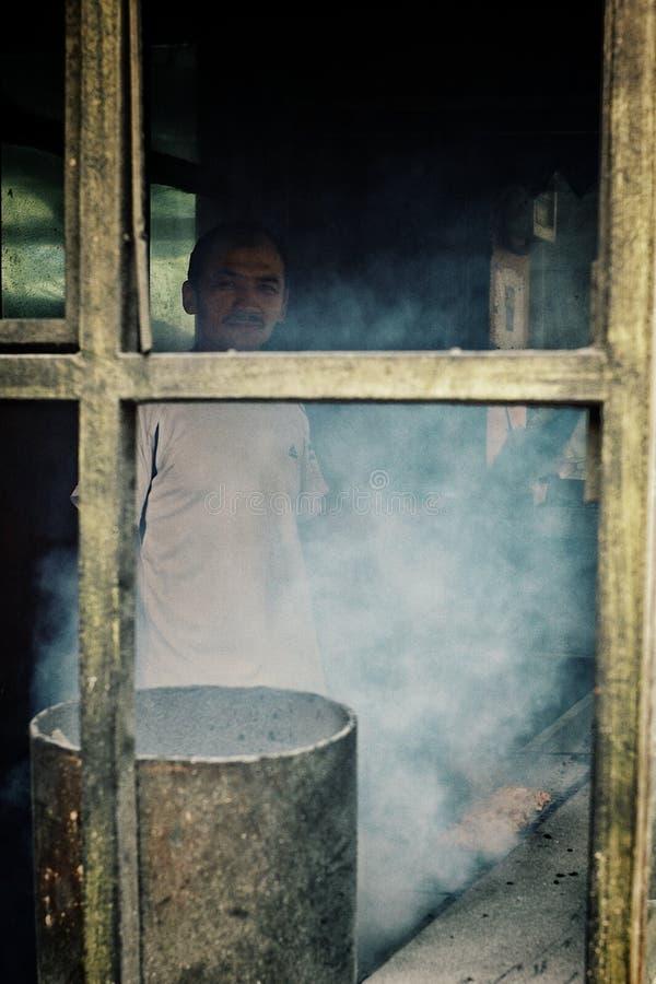 equipaggi la cottura dell'alimento della via ad un mercato locale con fumo che copre il bruciatore fotografie stock