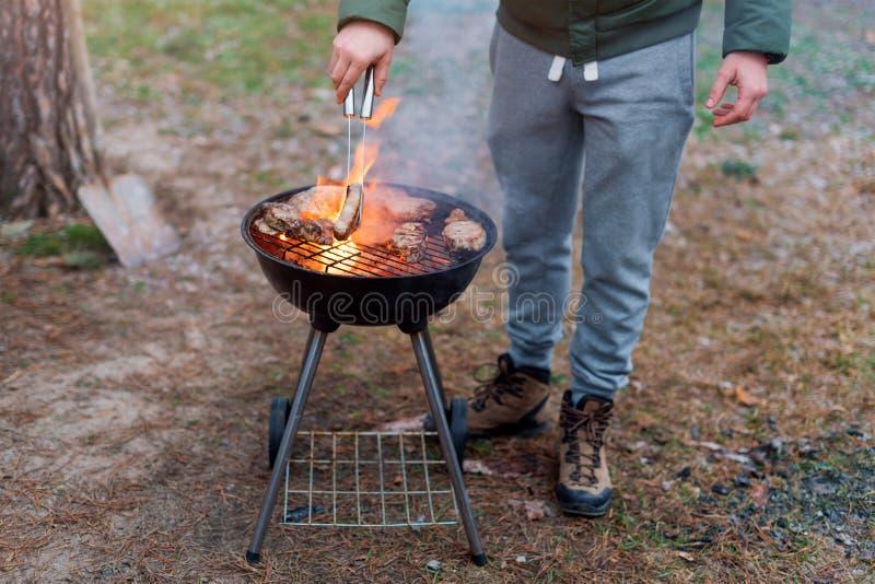 Equipaggi la cottura, solo le mani, lui sta grigliando la carne o la bistecca per un piatto Carne arrostita deliziosa sulla grigl immagine stock libera da diritti
