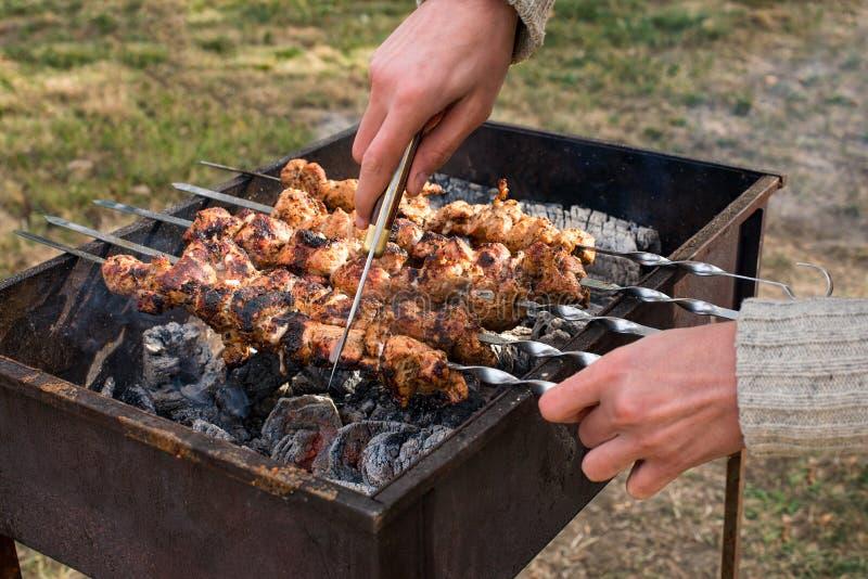 Equipaggi la cottura, solo le mani, lui sta tagliando la carne o la bistecca per un piatto Carne arrostita deliziosa sulla grigli fotografia stock