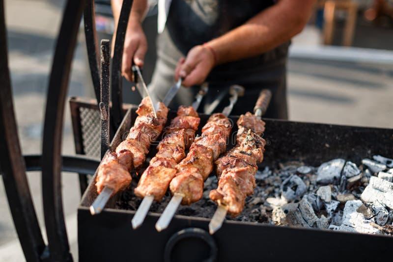 Equipaggi la cottura, solo le mani, lui sta tagliando la carne o la bistecca per un piatto Griglia deliziosa Fine settimana del b immagini stock libere da diritti