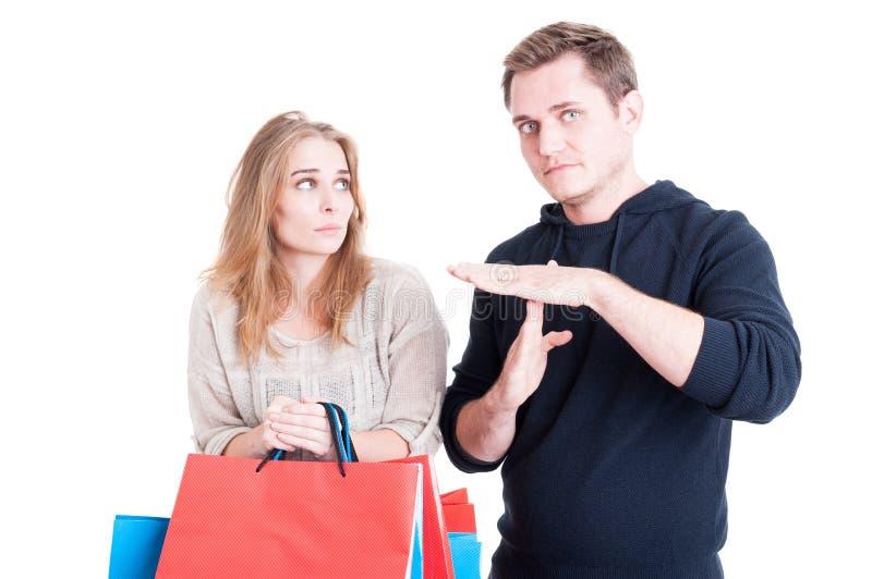 Equipaggi la fabbricazione del tempo fuori gesture ai sacchetti della spesa della tenuta della donna immagine stock libera da diritti