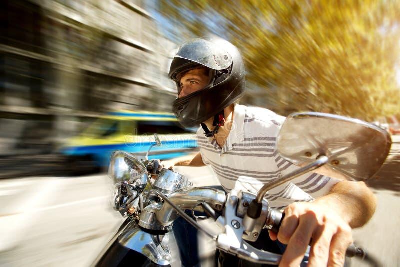 Equipaggi la guida del motorino alla velocità sulla strada con fondo vago fotografia stock
