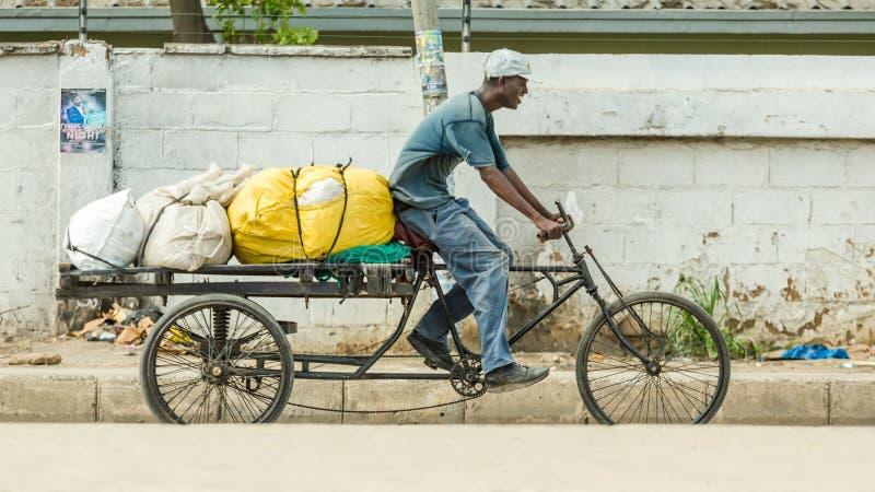 Equipaggi la guida della sua bicicletta su misura misura con un rimorchio caricato fotografia stock libera da diritti