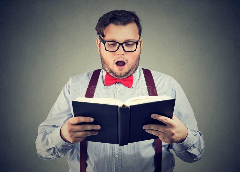 Equipaggi la lettura del libro interessante con l'espressione colpita del fronte fotografia stock