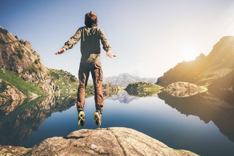 Equipaggi la levitazione di salto di volo con il lago e le montagne su fondo immagini stock