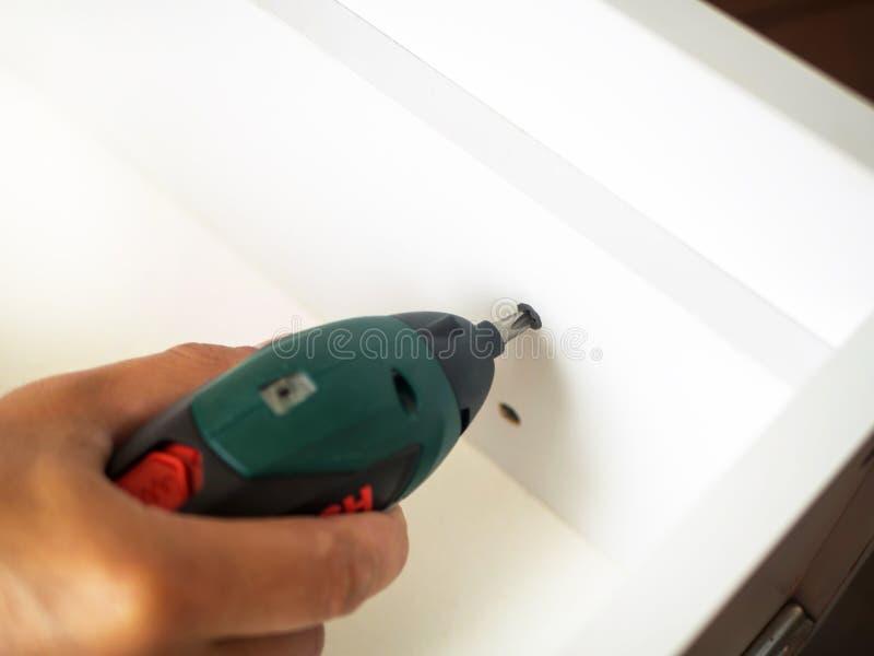 Equipaggi la mano che tiene il cacciavite elettrico e che avvita la vite in immagine stock libera da diritti