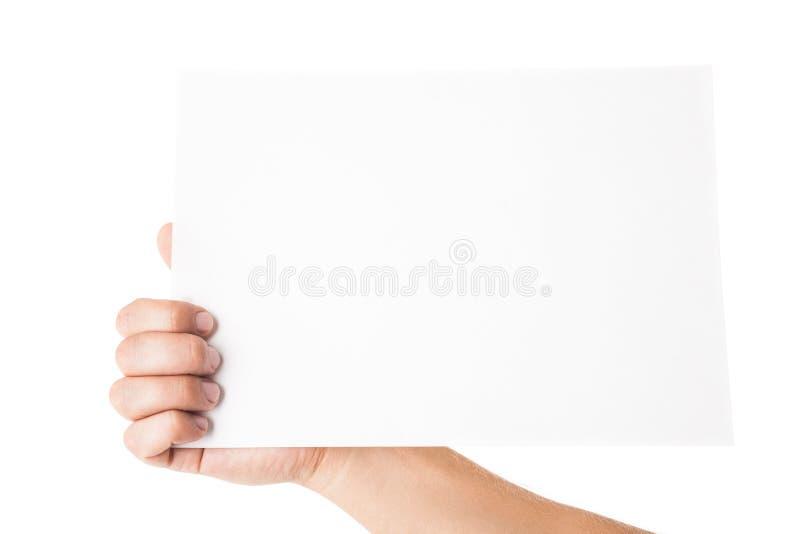 Equipaggi la mano che tiene la carta di pubblicità in bianco su bianco fotografia stock libera da diritti
