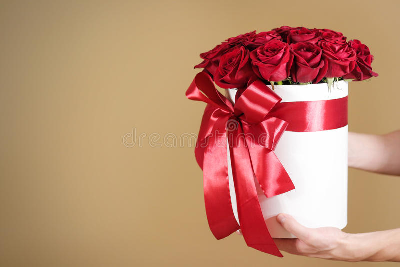 Equipaggi la mano che tiene un mazzo ricco del regalo di 21 rosa rossa composizione fotografia stock libera da diritti