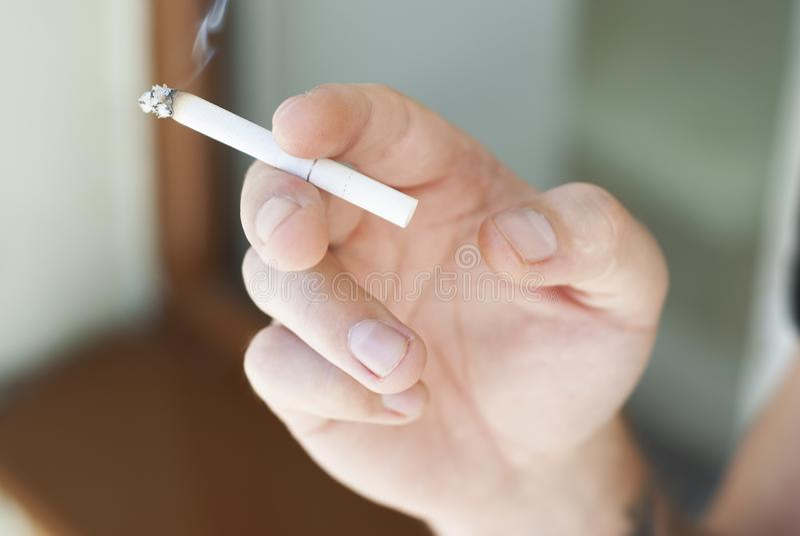 Equipaggi la mano che tiene una sigaretta con il fuoco selettivo del fumo fotografie stock libere da diritti