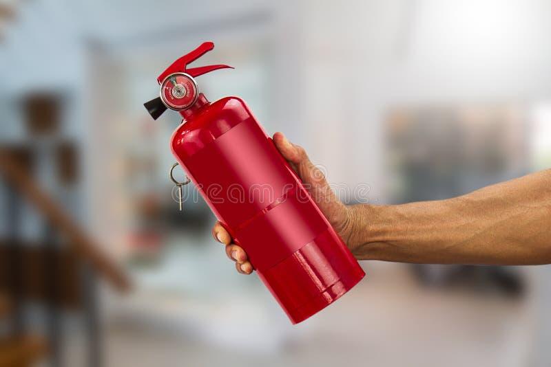 Equipaggi la mano del ` s che tiene l'estintore pratico sul fondo vago della casa fotografia stock