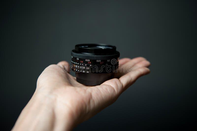 Equipaggi la mano del ` s che tiene un obiettivo su un fondo nero fotografia stock