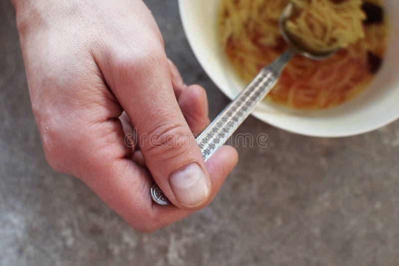 Equipaggi la mano del ` s con il cucchiaio ed il piatto bianco immagine stock libera da diritti