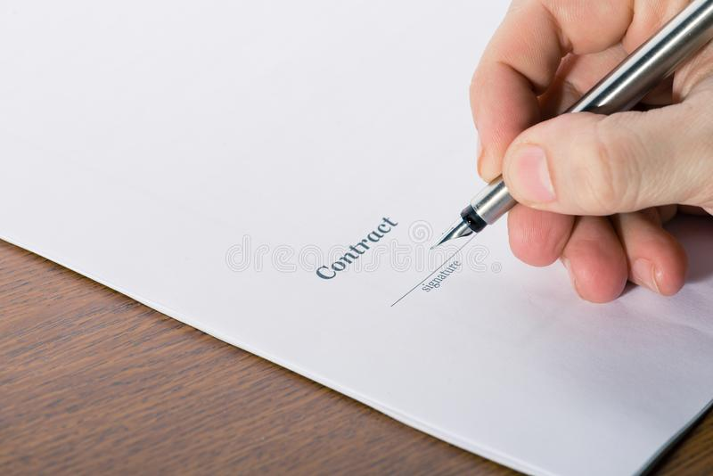 Equipaggi la mano del ` s con un segno della penna un contratto fotografia stock libera da diritti