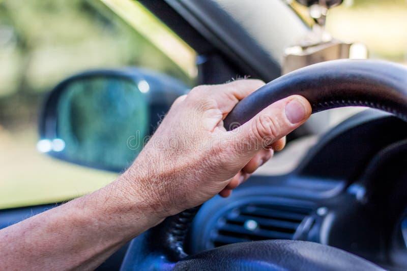 Equipaggi la mano del ` s sul volante di un'automobile Guidando sul road_ fotografia stock