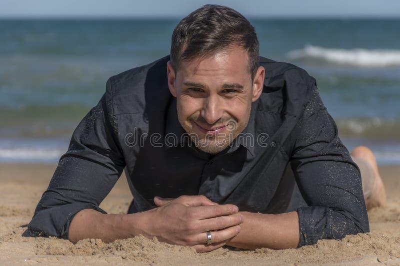 Equipaggi la menzogne sulla sabbia sulla spiaggia che esamina la macchina fotografica immagini stock