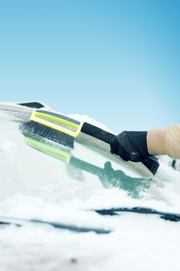 Equipaggi la neve di pulizia dal parabrezza dell'automobile con la spazzola fotografia stock libera da diritti