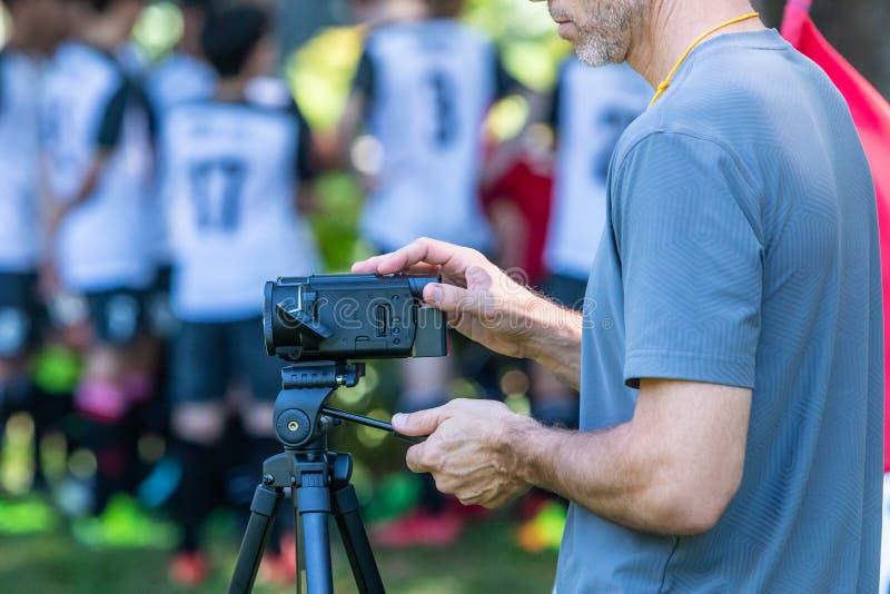 Equipaggi la partita di calcio della registrazione con la sua videocamera su un treppiede a fotografie stock libere da diritti