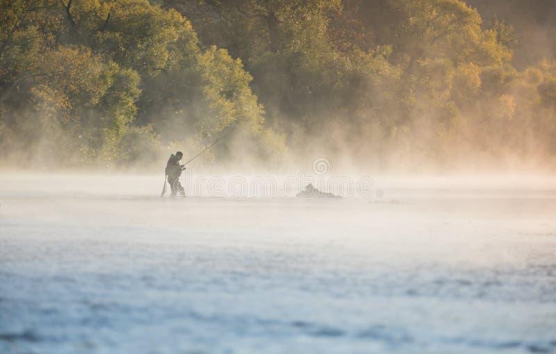 Equipaggi la pesca nel fiume con la barretta di mosca nel corso della mattinata dell'estate immagini stock