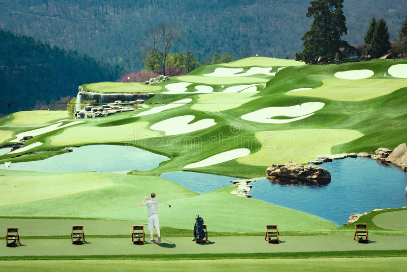 Equipaggi la pratica dei suoi colpi di golf su un bello campo da golf fotografia stock libera da diritti