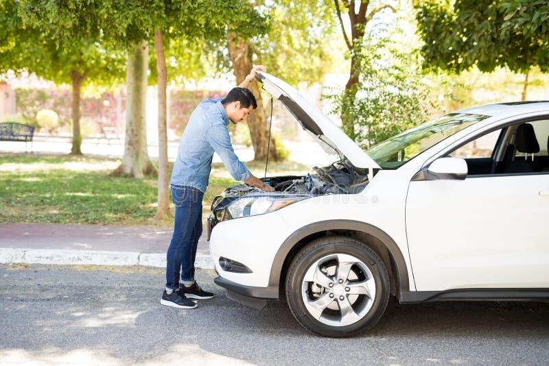 Equipaggi la prova di riparare l'automobile sulla strada fotografia stock