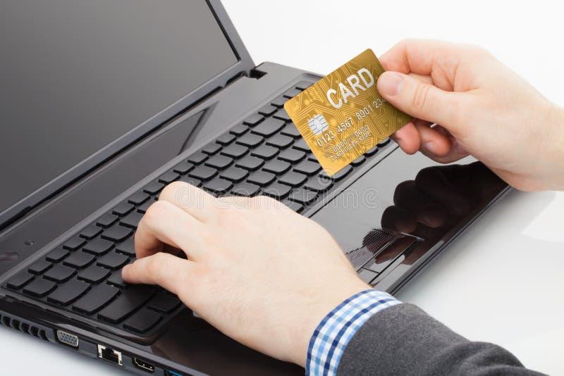 Equipaggi la prova di usare la sua carta di credito dorata per pagare qualcosa online fotografia stock libera da diritti