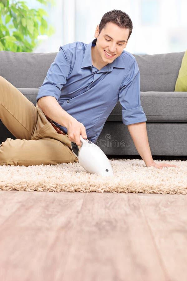 Equipaggi la pulizia del suo tappeto con un aspirapolvere tenuto in mano fotografia stock libera da diritti