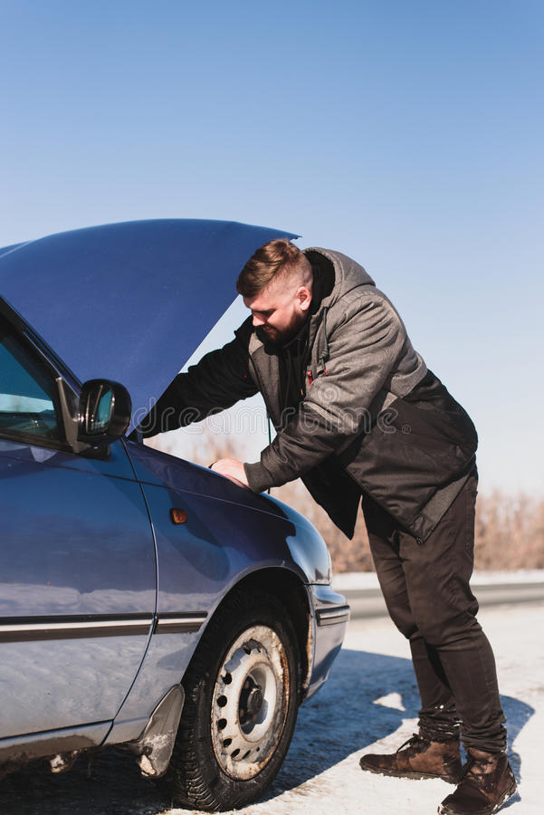 Equipaggi la riparazione dell'automobile che sta al cappuccio immagini stock libere da diritti