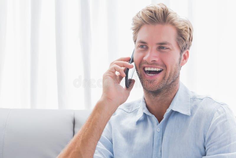 Equipaggi la risata mentre è sul telefono immagine stock