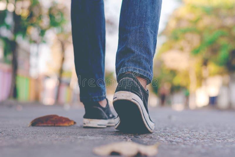 Equipaggi la scarpa da tennis ed i jeans d'uso che camminano lungo la via della città immagine stock libera da diritti