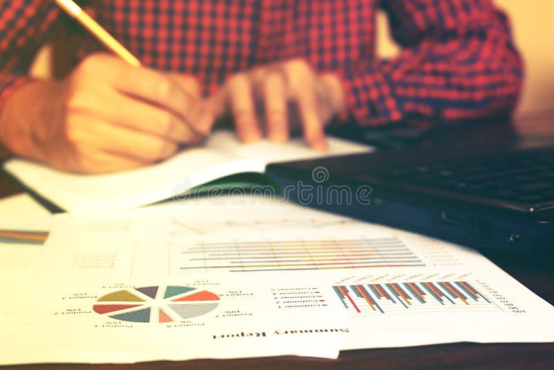 Equipaggi la scrittura e faccia la nota circa l'annuale e le spese di costo a casa fotografia stock libera da diritti