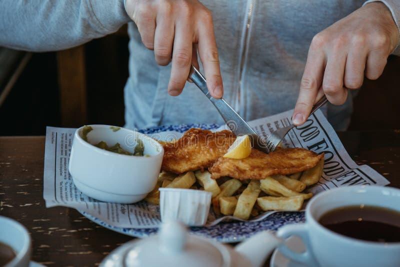 Equipaggi la seduta alla tavola di legno, mangiante il pesce e patate fritte immagini stock