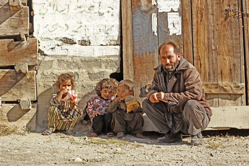 Equipaggi la seduta con i suoi bambini e sorridere nel distretto dello schiaffo immagini stock