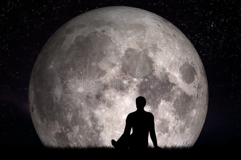 Equipaggi la seduta da solo sull'erba e considerare la luna Immagini il concetto futuro immagine stock libera da diritti