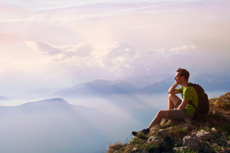 Equipaggi la seduta sopra la montagna, il risultato o il concetto di opportunità, viandante fotografie stock