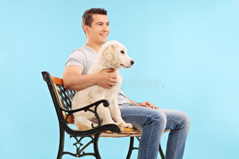 Equipaggi la seduta sul banco con un giovane cane fotografie stock libere da diritti