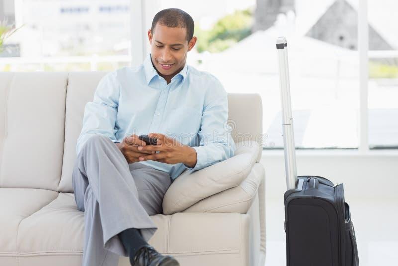Equipaggi la seduta sul sofà che invia un testo che aspetta per partire sul viaggio di affari fotografia stock