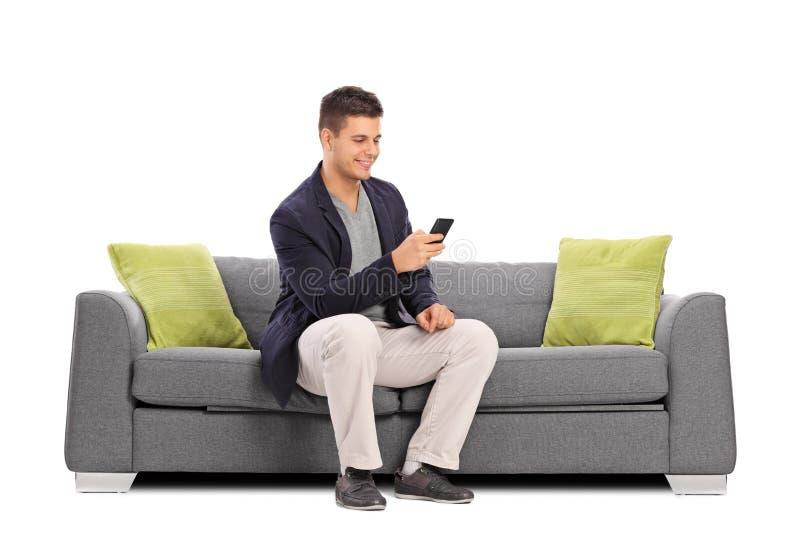 Equipaggi la seduta sul sofà e la battitura a macchina sul suo telefono cellulare immagine stock libera da diritti