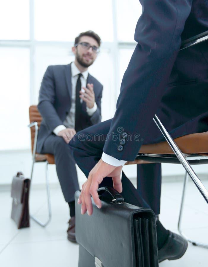 Equipaggi la seduta sulla sedia in ufficio che ascolta l'uomo d'affari di affari fotografia stock libera da diritti