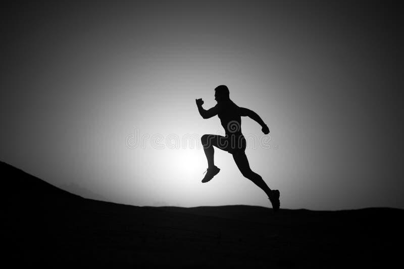 Equipaggi la siluetta corrente al tramonto, giovane caucasian fatto funzionare in mountai fotografie stock