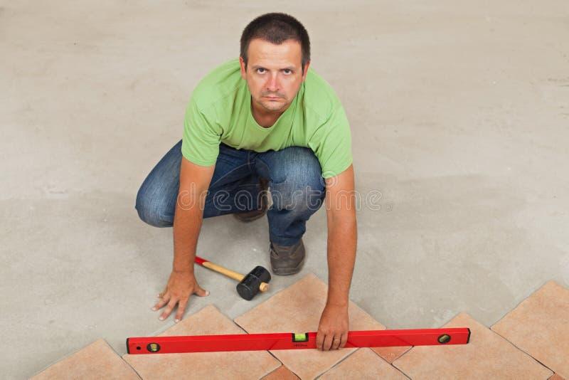 Equipaggi la stenditura delle piastrelle per pavimento ceramiche - controllando con una vista livellata e superiore fotografia stock