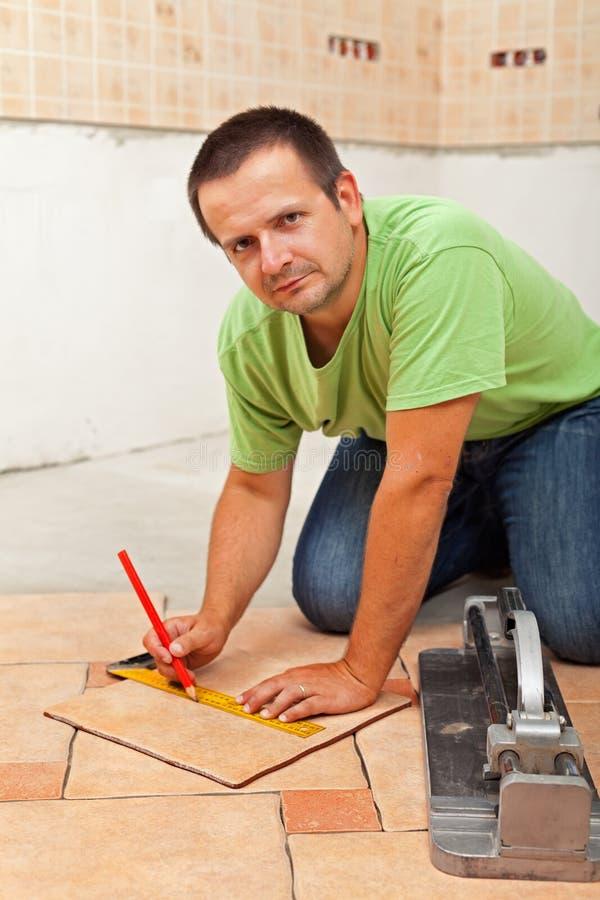 Equipaggi la stenditura delle piastrelle per pavimento ceramiche - misurando e tagliando l'un pezzo solo fotografie stock libere da diritti