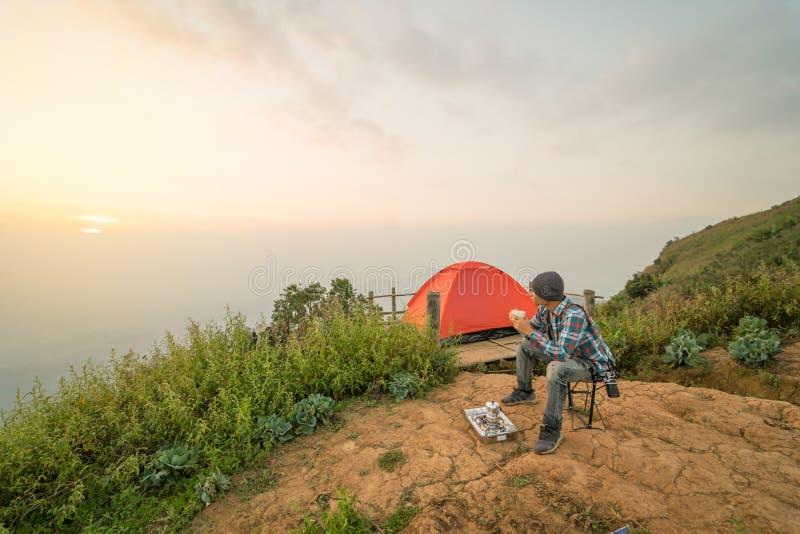 Equipaggi la tenda di campeggio vicina di seduta e bevente del caffè immagini stock libere da diritti