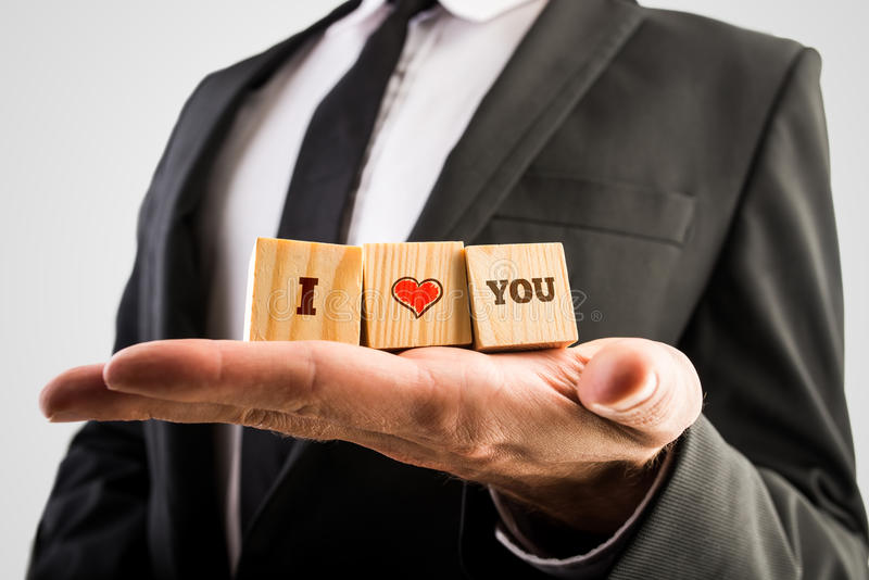 Equipaggi la tenuta dei blocchi di legno con ti amo il messaggio e un a mano DRA immagine stock