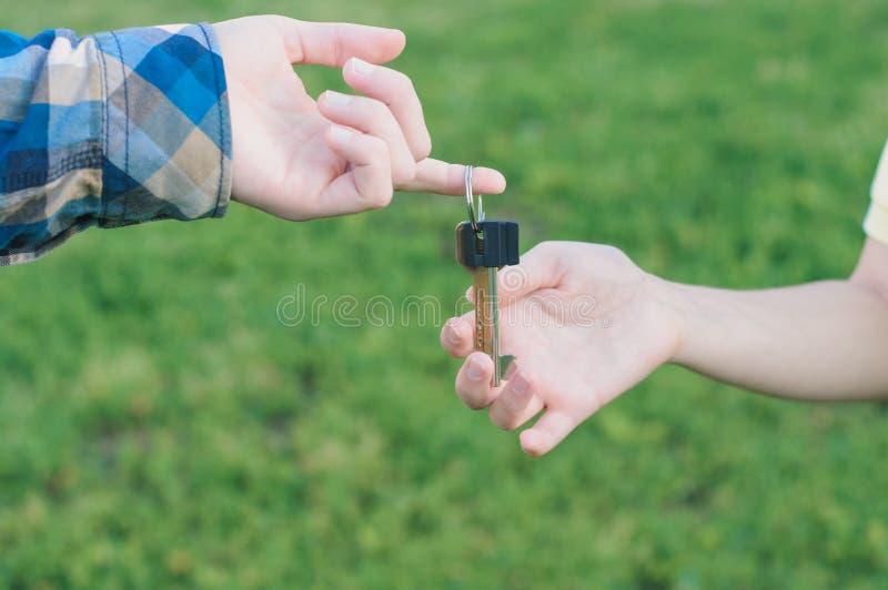Equipaggi la tenuta della chiave dalla nuova casa in mani fotografia stock libera da diritti