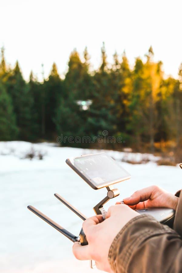Equipaggi la tenuta nel suo trasmettitore a distanza della leva di comando del regolatore delle mani che pilota il fuco con il gi immagine stock