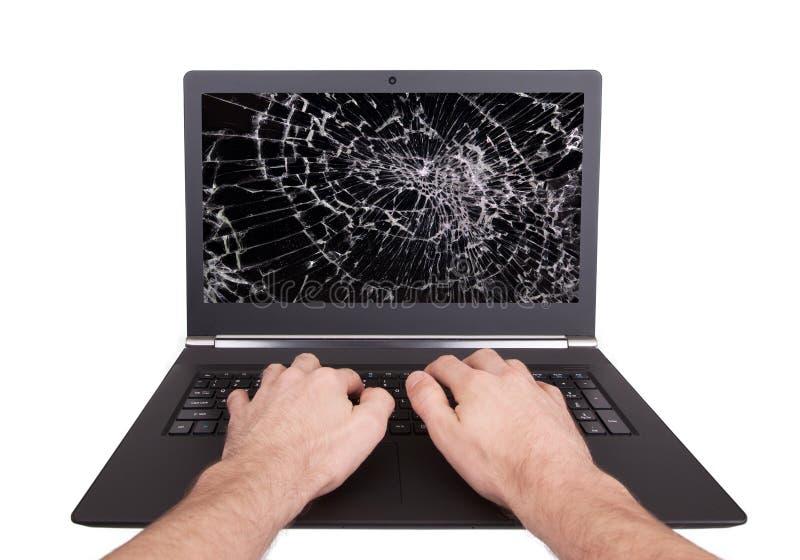 Equipaggi lavorare ad un computer portatile con uno schermo rotto immagini stock