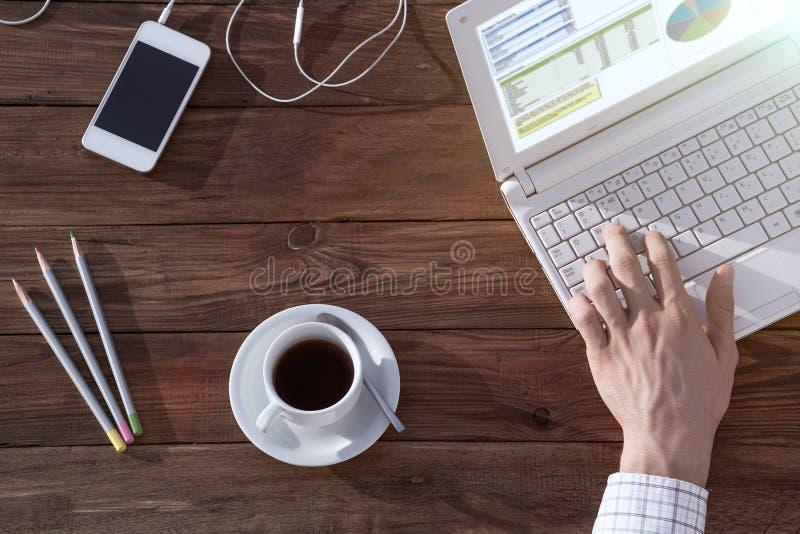 Equipaggi lavorare al computer alla visualizzazione sopraelevata dello scrittorio di legno fotografia stock