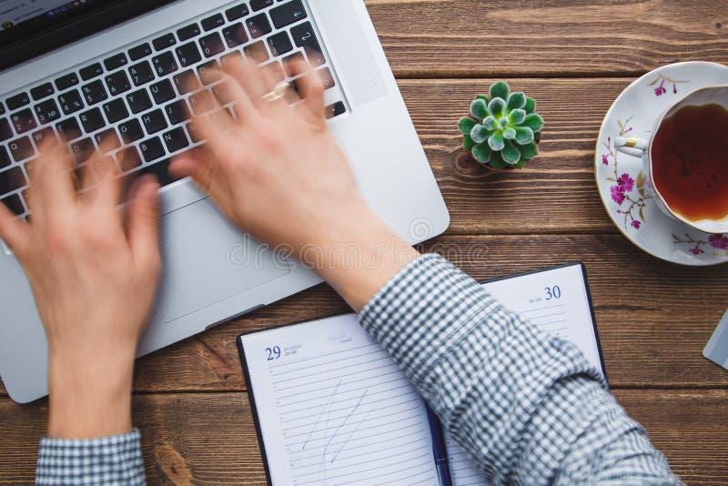 Equipaggi lavorare al computer portatile disposto sullo scrittorio di legno fotografia stock libera da diritti